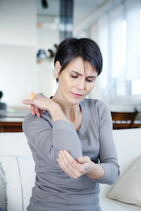 Woman dealing with pain from tennis elbow
