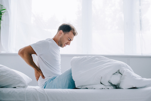 Man dealing with back pain and unable to sleep